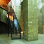 Large room with stone walls a metal staircase and a small blueish haze of light mounting staircase