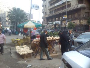 man walking past a timber table with lots of Egyptian bread on it, protected by a beach umbrella