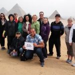 group of 14 people with three pyramids in the background