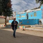 Mara - owner of Mara House and Mara House Tours alking through street with elaborately decorated house painted blue, in Nubian Village, Aswan