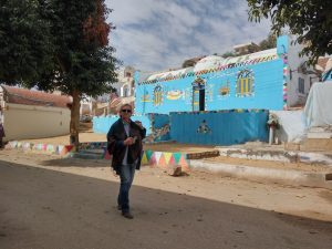 Mara walking through street with elaborately decorated house painted blue, in Nubian Village, Aswan