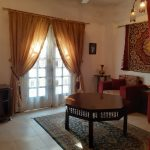 living room, two comfortable red armchairs, large red/yellow arabian wall hanging, double doors opening to balcony, large table stands in the centre of room on oriental rug, beige floor tiles. Light & airy ambiance
