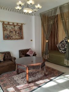 romantic day bed behind long, transparent curtains, green bedcover and large patchwork cushions, 2 brown leather armchairs, sturdy low wooden octagonal table on oriental floor rug