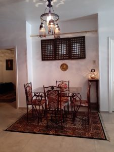 Private dining area has glass top table and four chairs - arabian lighting and decorative mashrabeya window covering provides a romantic, private ambiance