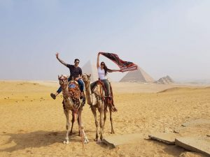 young lade on a camel waving a long scarve behind her head. Beside her on a young man on a camel. In the desert with 3 pyramids in the background