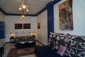 Very large bedroom - double bed, side lockers with lamps on them, sitting area with 3 big patchwork cushions having geometric design in various colours, paintings and wall hanging on the wall