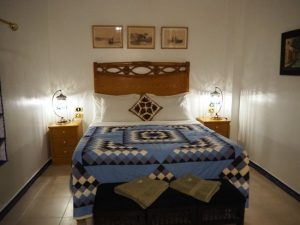Double bed covered with patchwork quilt in blue, white and navy. 3 scenic pictures over the bed